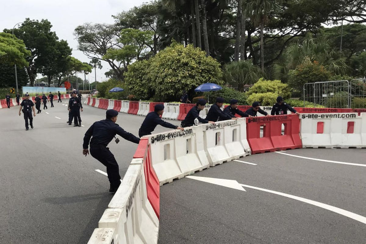 Police officers move barricades at Changi Airport ahead of Mr Kim's arrival.