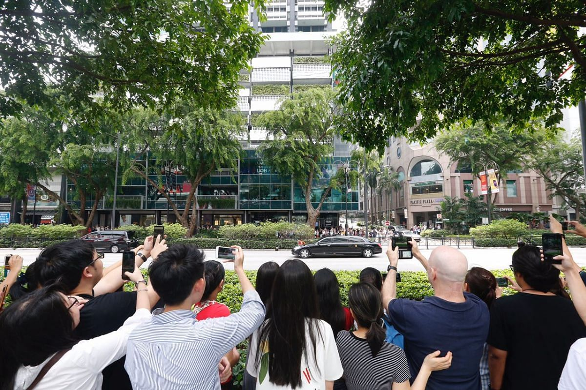 Members of the public taking photos of Mr Kim's convoy.
