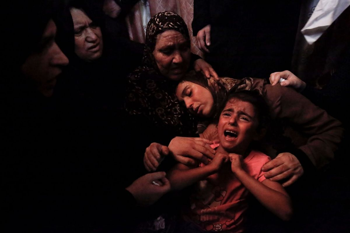 The mother (C) and unidentified relatives of 15-year-old Haitham al-Jamal mourn over his death during his funeral in Rafah in the southern Gaza Strip on June 9, 2018, one day after he was fatally shot by Israeli soldiers. PHOTO: AFP