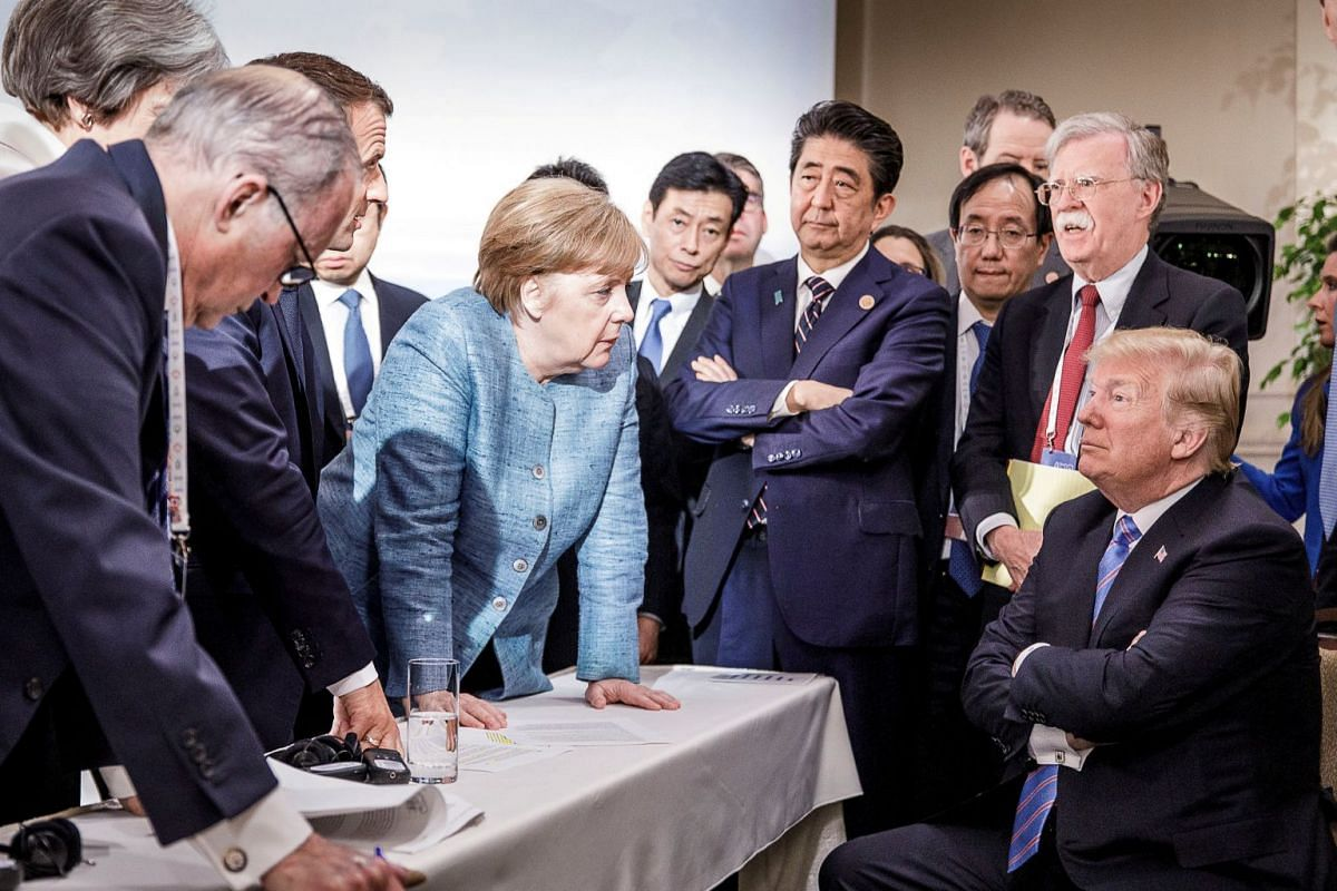 German Chancellor Angela Merkel speaks to U.S. President Donald Trump during the second day of the G7 meeting in Charlevoix city of La Malbaie, Quebec, Canada, June 9, 2018. PHOTO: BUNDESREGIERUNG HANDOUT VIA REUTERS