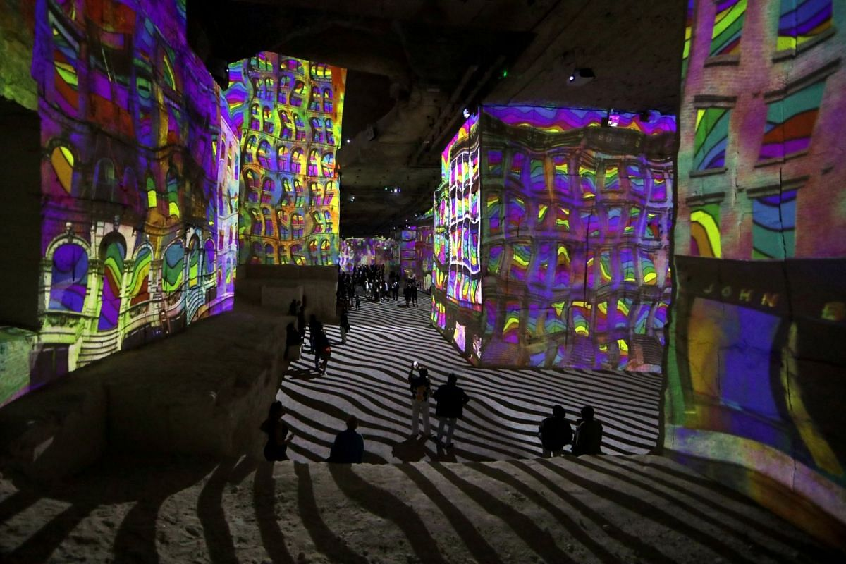 People look at projected images of artwork on the limestone surfaces of the former quarry 'Carrieres des Lumieres' as part of Pablo Picasso's multimedia exhibition in Les Baux-De-Provence, France, June 9, 2018. PHOTO: REUTERS
