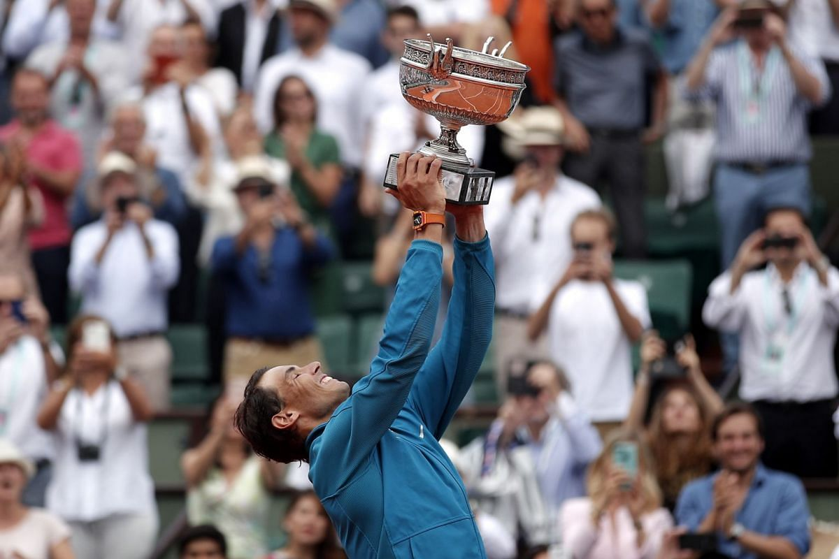 Rafael Nadal of Spain celebrates with the trophy after winning his 11th French Open title against Dominic Thiem of Austria during their men's final match during the French Open tennis tournament at Roland Garros in Paris, France, June 10, 2018. PHO