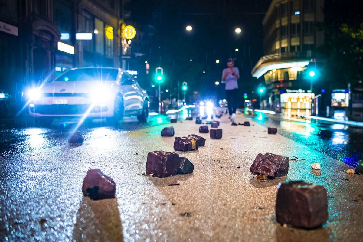 People walk past loose pavement stone pieces on a street after heavy rain in Lausanne, Switzerland, early June 12, 2018, as heavy rain and thunder storms hit the city. PHOTO: EPA-EFE