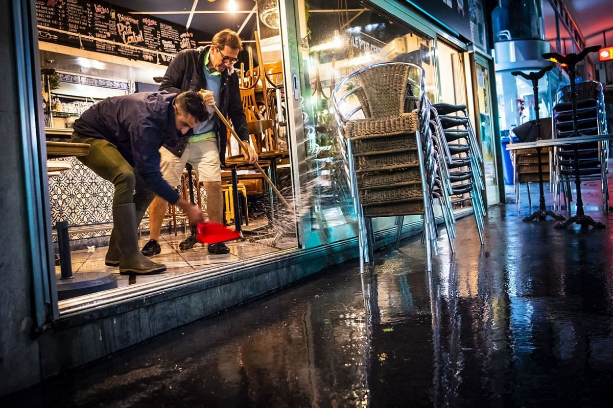 Men clean the floor of their restaurant that was flooded after heavy rain in Lausanne, Switzerland, early  June 12, 2018, as heavy rain and thunder storms hit the city. PHOTO: EPA-EFE