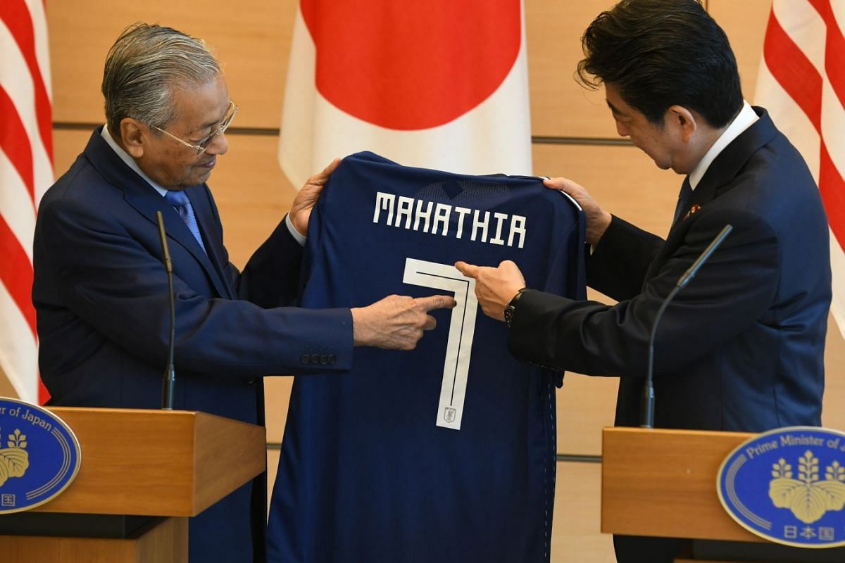 Malaysian Prime Minister Mahathir Mohamad (L) receives a present of Japanese national football jersey from his Japanese counterpart Shinzo Abe (R) during their joint press remarks at Abe's official residence in Tokyo, Japan, June 12, 2018. PHOTO: EPA