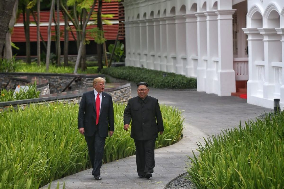 US President Donald Trump and North Korean leader Kim Jong Un share a light moment as they stroll through the courtyard of Capella Singapore after their meeting.