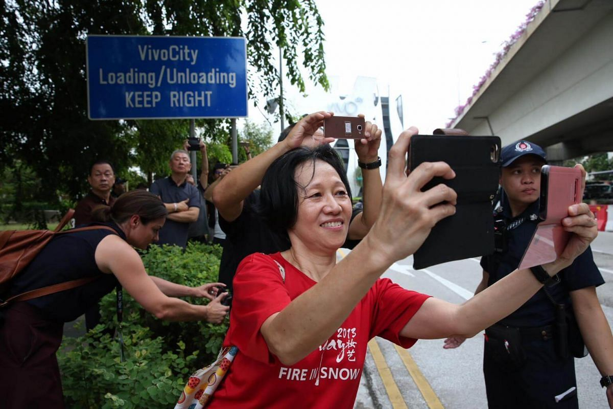Members of the public trying to get pictures of US President Donald Trump and North Korean leader Kim Jong Un's motorcades as they make their way to Sentosa, on June 12, 2018.