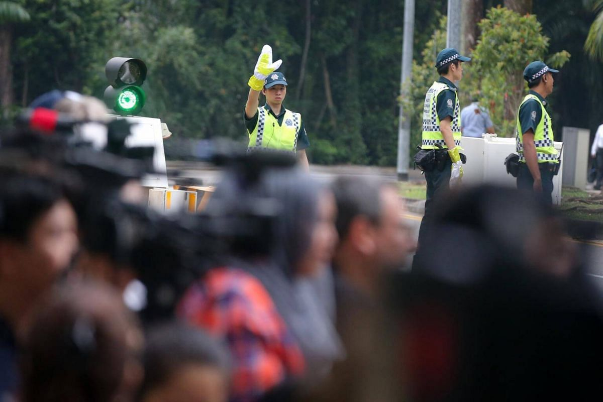 Auxiliary police directing traffic as the international media wait for US President Donald Trump to leave Shangri-La Hotel, Singapore, on June 12, 2018.