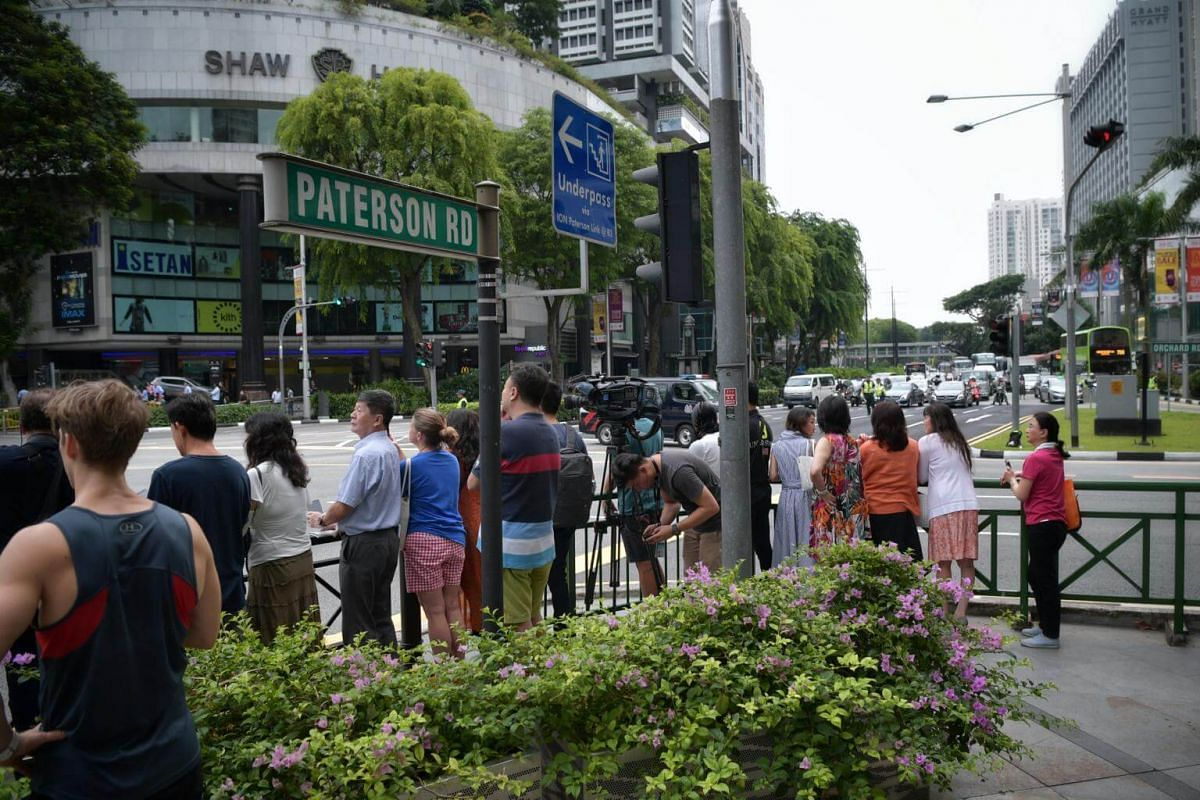 Members of the public gather at the junction of Orchard Road and Paterson Road to spot the motorcades of US President Donald Trump and North Korean leader Kim Jong Un on June 12, 2018.