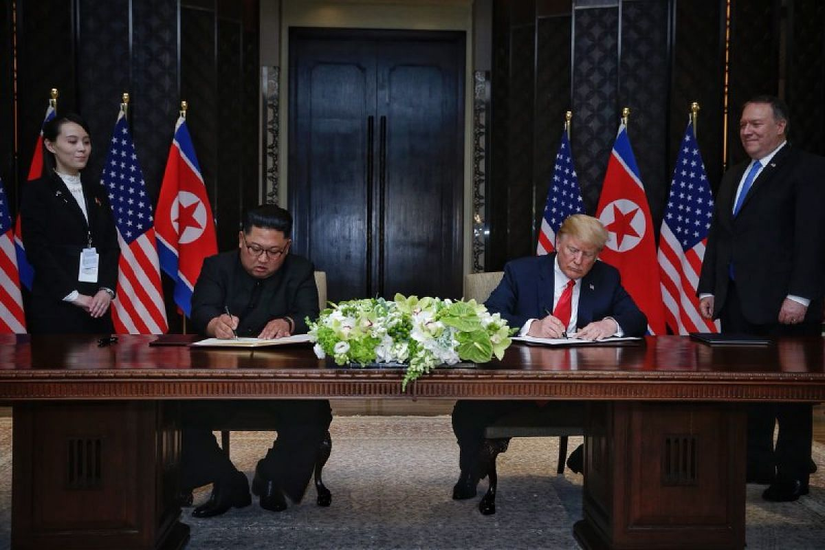 """US President Donald Trump and North Korean leader Kim Jong Un sign a """"comprehensive"""" document at the end of their summit, on June 12, 2018."""