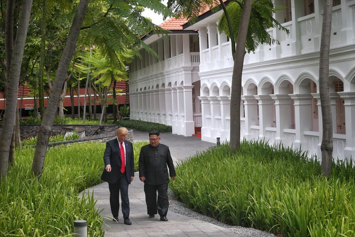 US President Donald Trump points out remote cameras planted along the path to North Korean leader Kim Jong Un as they stroll through the courtyard of Capella Singapore.