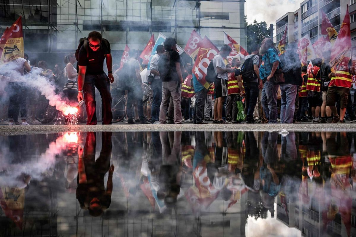 French railway workers are reflected in a puddle as they demonstrate with banners, flags and flares in Lyon, east-central France, on June 12, 2018, on the 15th day of rolling train strikes since April against the planned overhaul of French national r