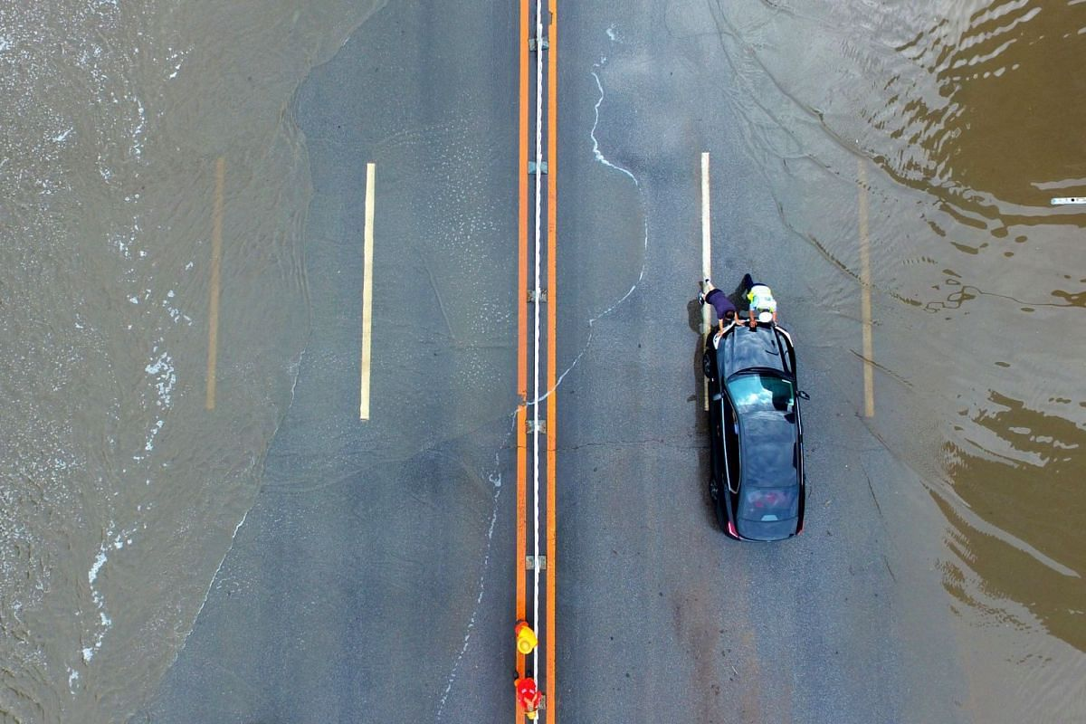 This aerial photo taken on June 11, 2018 shows a police officer (R) helping a driver pushing his car on a water-logged street after heavy rainfall in Shenyang in China's northeastern Liaoning province. PHOTO: AFP