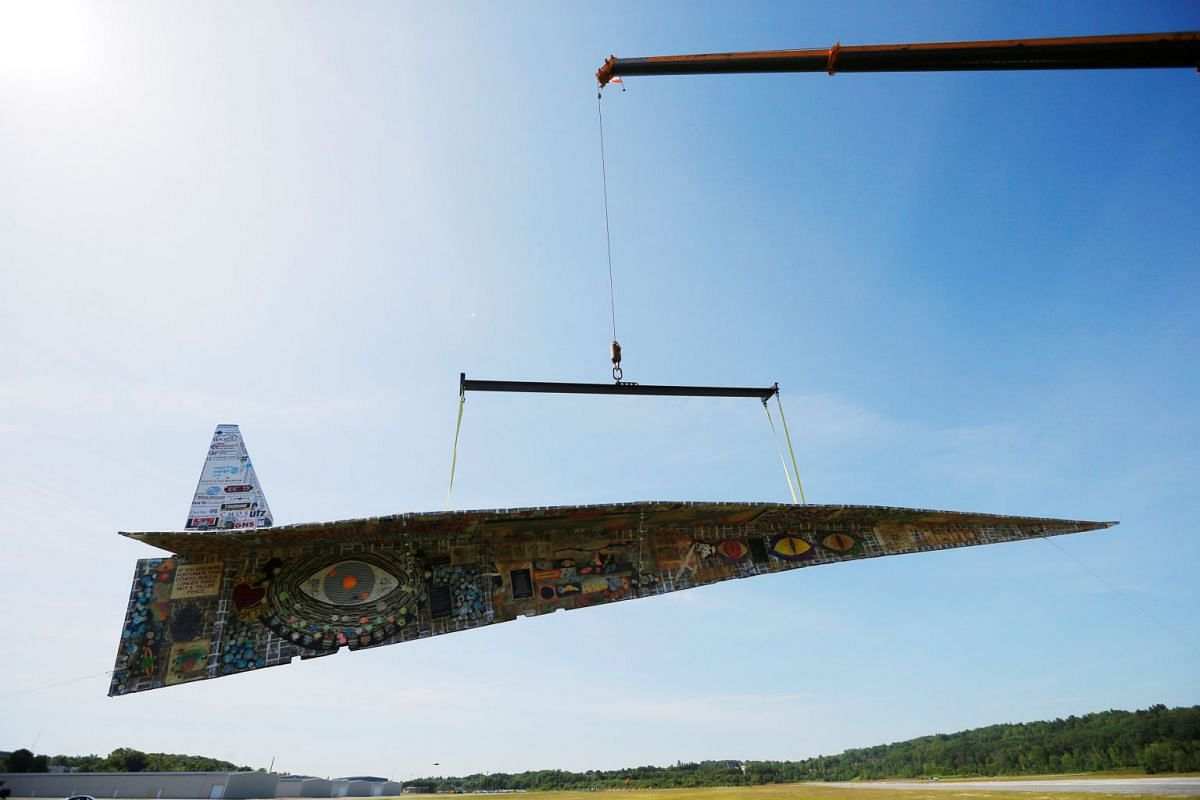 The Revolving Museum's 64-plus foot long paper airplane, a bid for entry into the Guinness Book of World Records for the world's largest paper airplane, is suspended from a crane in Fitchburg, Massachusetts, U.S., June 12, 2018. PHOTO: REUTERS