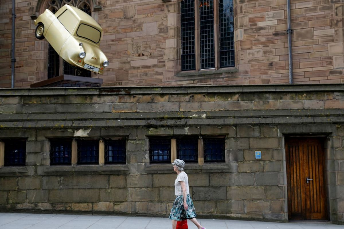 A woman walks past 'Gold Lamé' an installation by disabled artist Tony Heaton, in Liverpool, Britain, June 12, 2018. PHOTO: REUTERS
