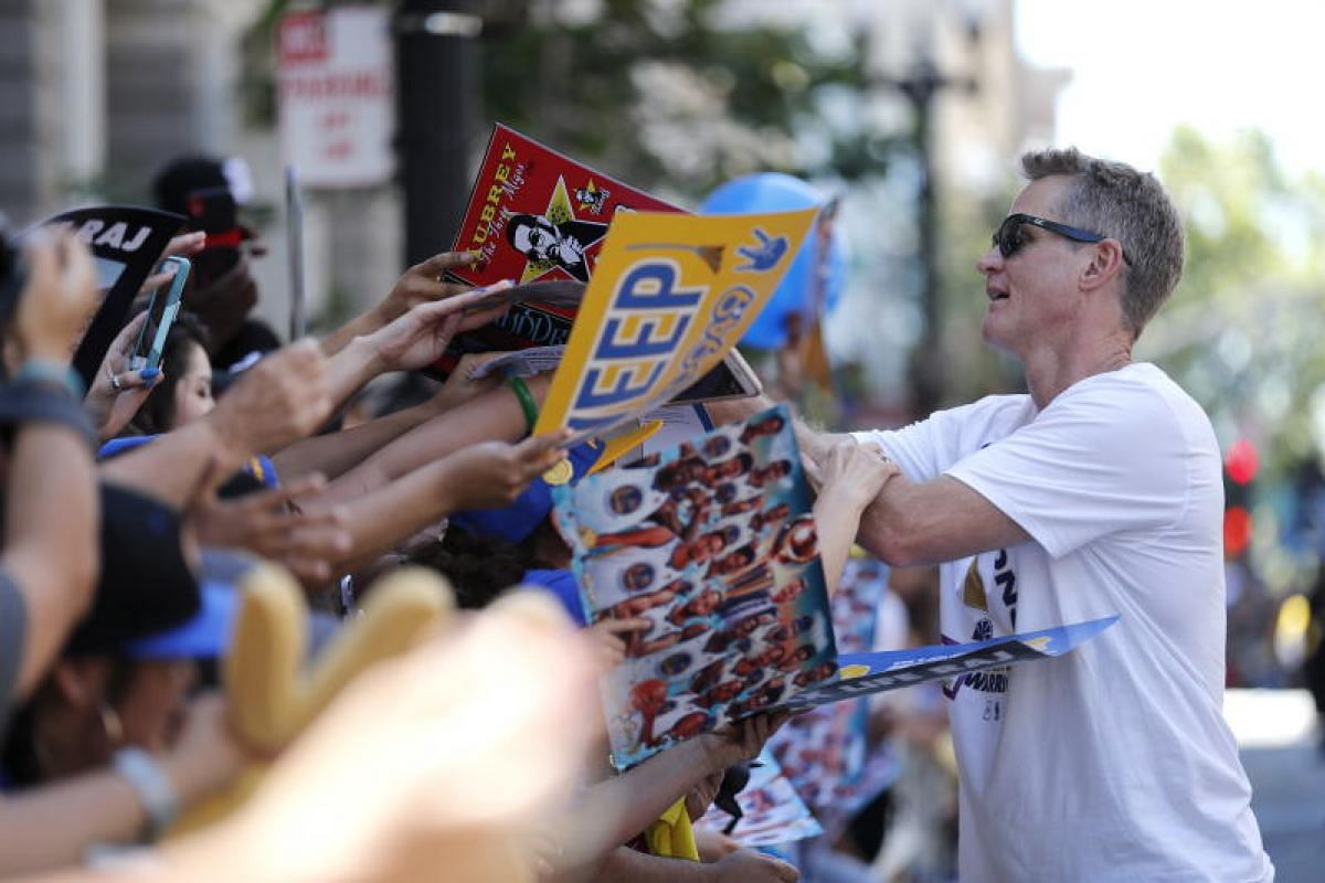 Golden State Warriors head coach Steve Kerr signs autographs along the route during the Golden State Warriors and the City of Oakland Championship parade to honour the 2018 NBA Champions in downtown Oakland, California, on June 12, 2018.