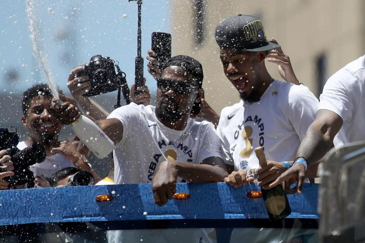 Kevin Durant (left) and Quinn Cook of the Golden State Warriors spray champagne from a bus as they celebrate during the Golden State Warriors Championship parade on June 12, 2018.