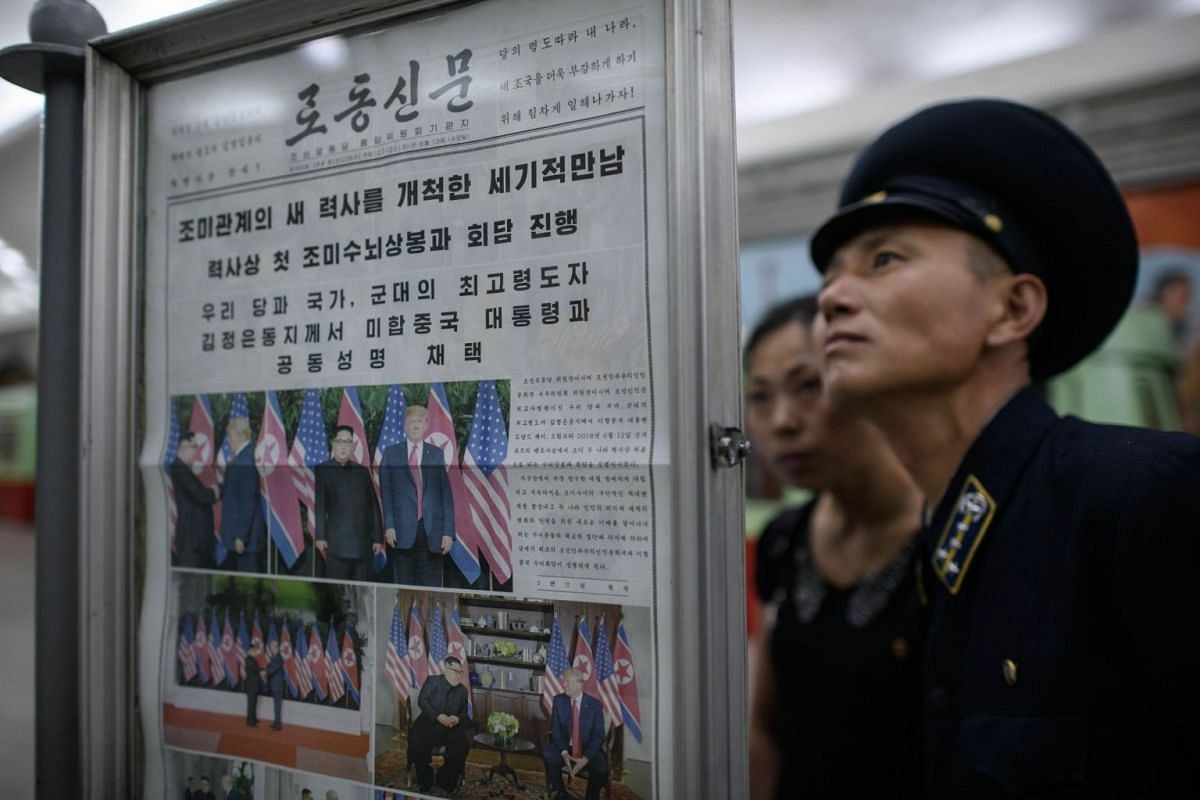 A conductor reads the latest edition of the Rodong Sinmun newspaper showing images of North Korean leader Kim Jong Un meeting with US president Donald Trump during their summit in Singapore, at a news stand on a subway platform of the Pyongyang metro