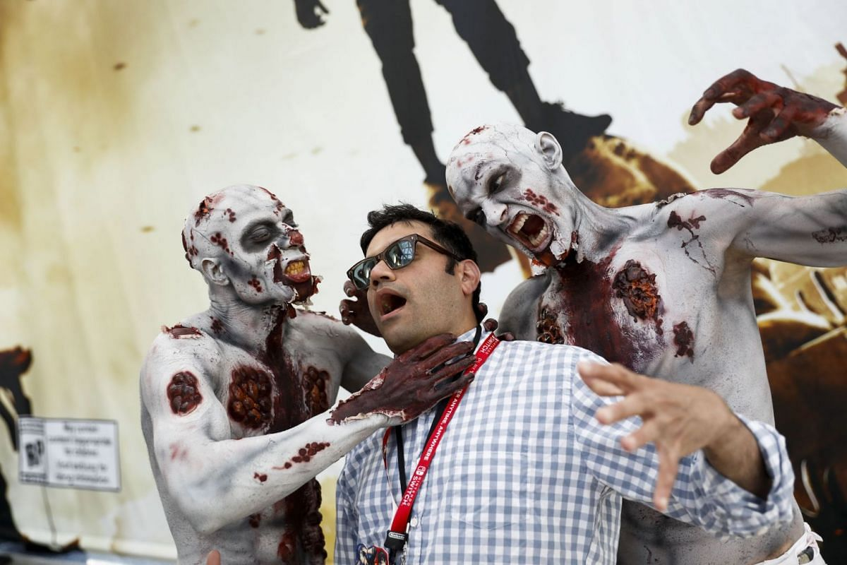 Actors dressed as a zombies from the Warner Bros. Interactive Entertainment Inc. Dying Light 2 video game interact with an attendee during the E3 Electronic Entertainment Expo in Los Angeles, California, U.S. on June 13, 2018. PHOTO: BLOOMBERG
