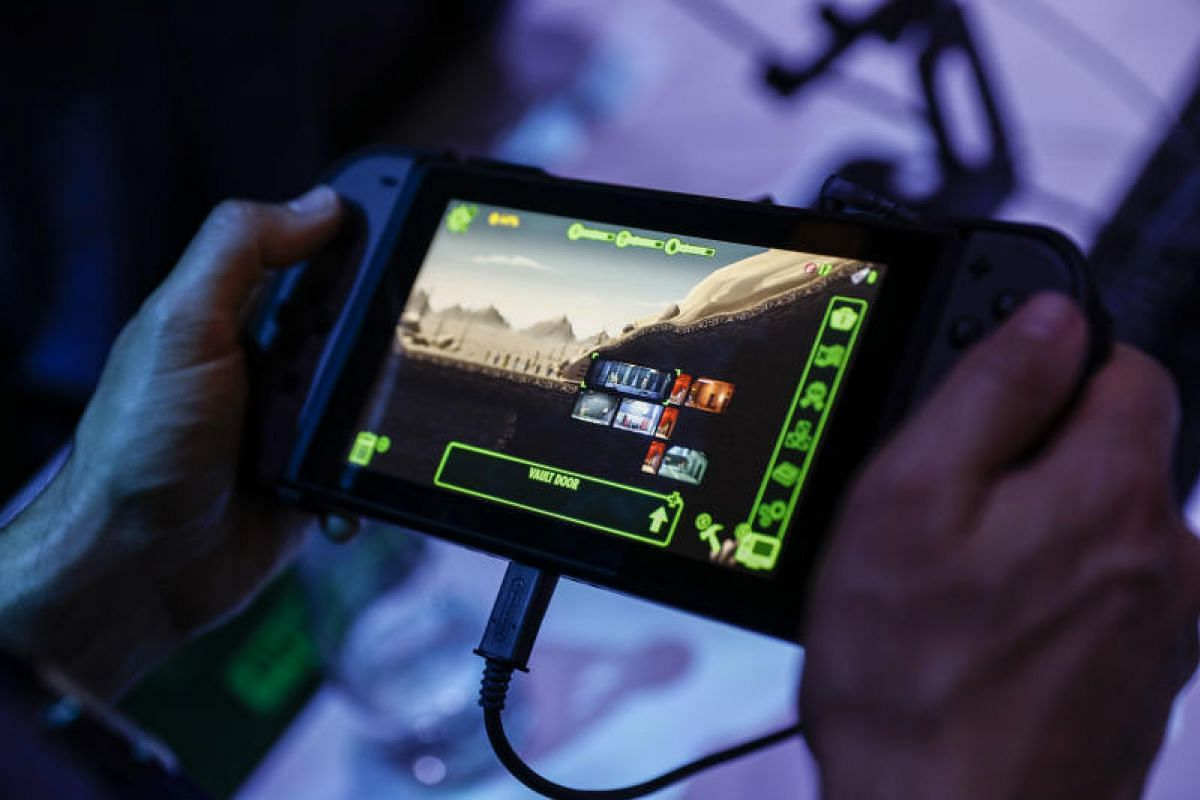 An attendee tries out another of Bethesda Softworks' video game, Fallout: Shelter, on the Nintendo Co. Switch console at E3.