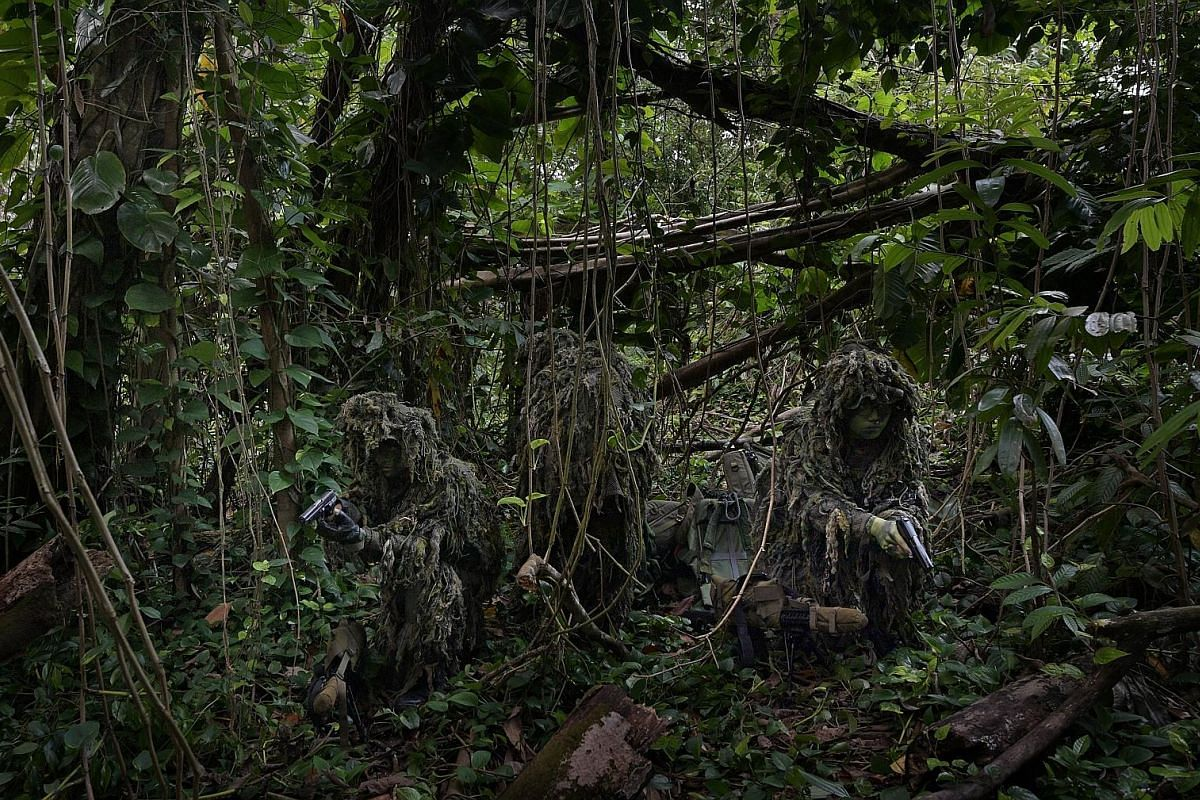 In the early hours of the morning, a sniper team moves along a gravel path to their training area. Wearing ghillie suits - a type of camouflage made from netting to which is attached strips of cloth - the snipers are able to break the defining featur