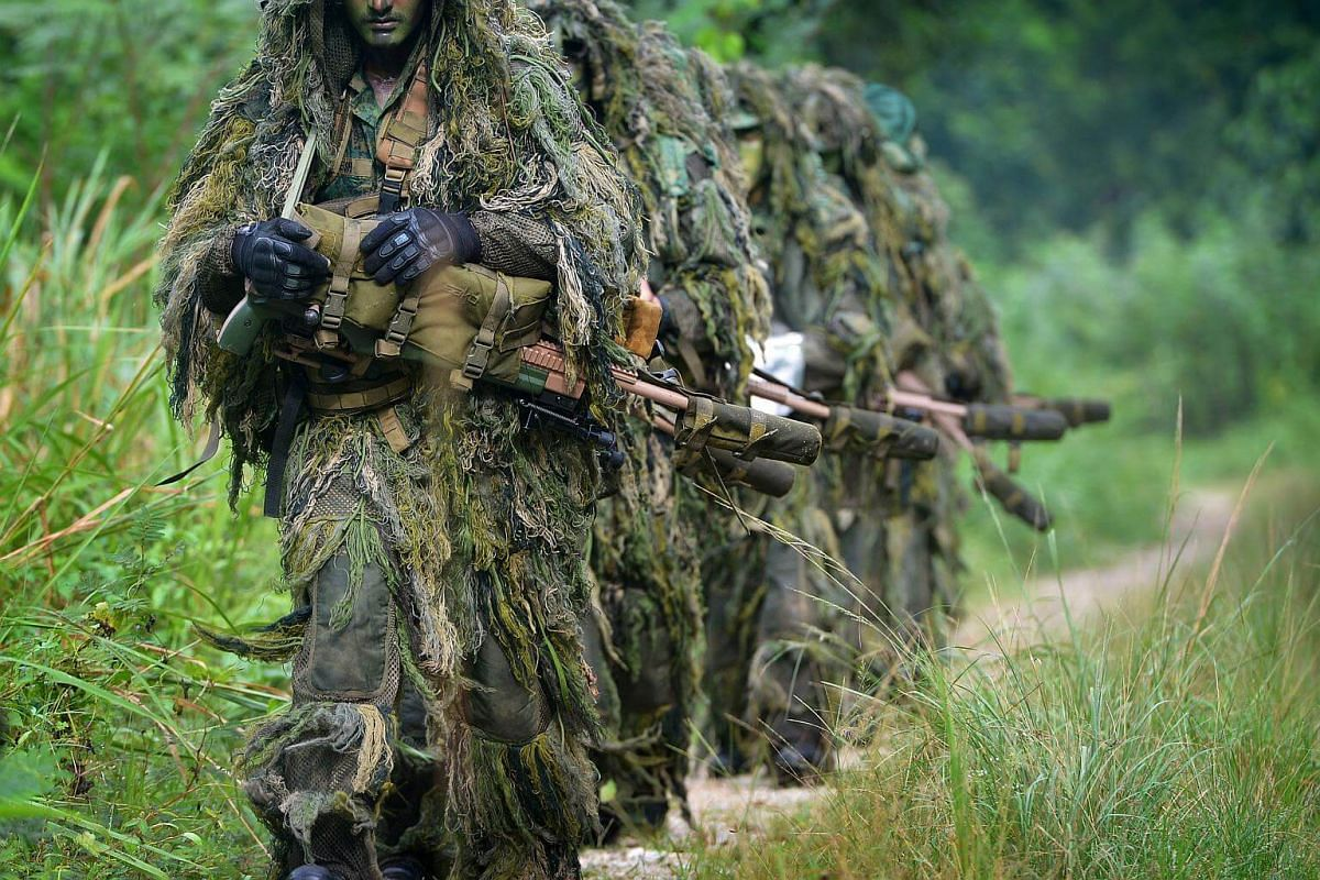 Clad in ghillie suits and covered in camouflage paint, a section of sniper trainees make their way to their training area carrying their weapons and field packs, which can weigh up to 40 kg.