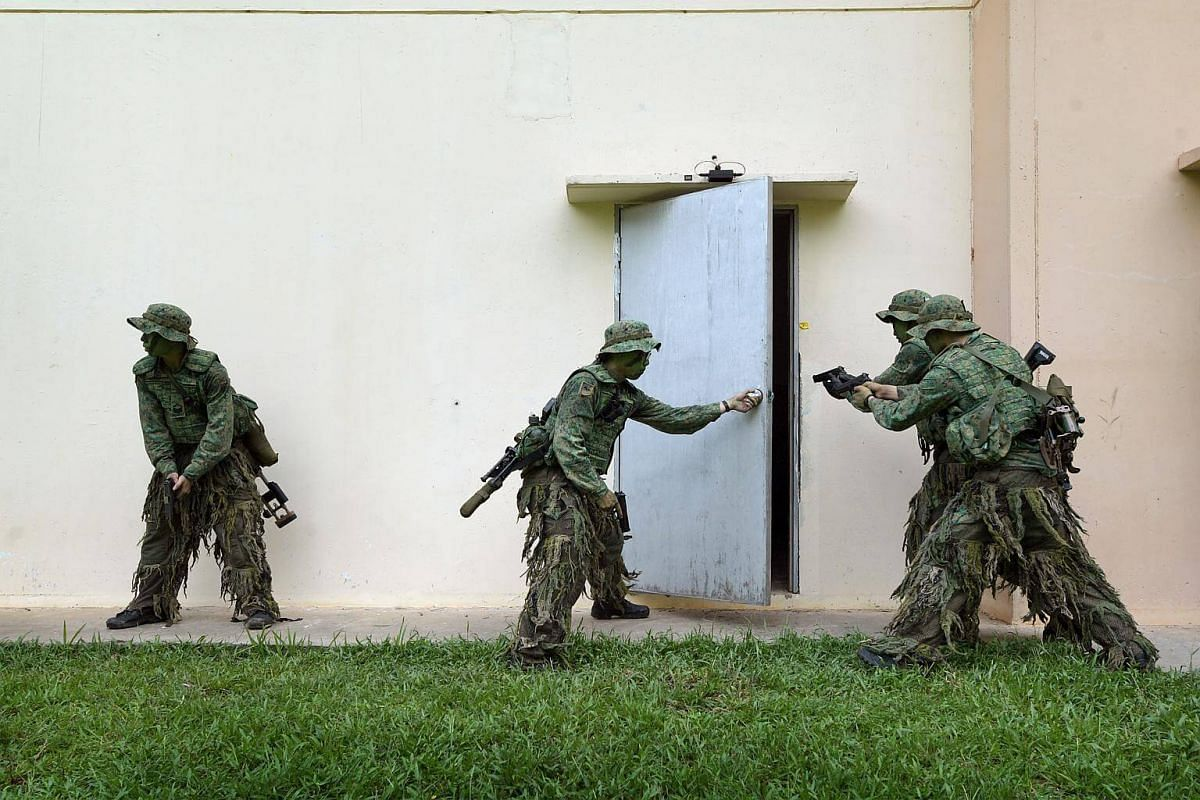 """A team of snipers practise entering a building via the back door. Using their pistols, the team must """"clear"""" the building of enemy before occupying it to set up their firing positions."""
