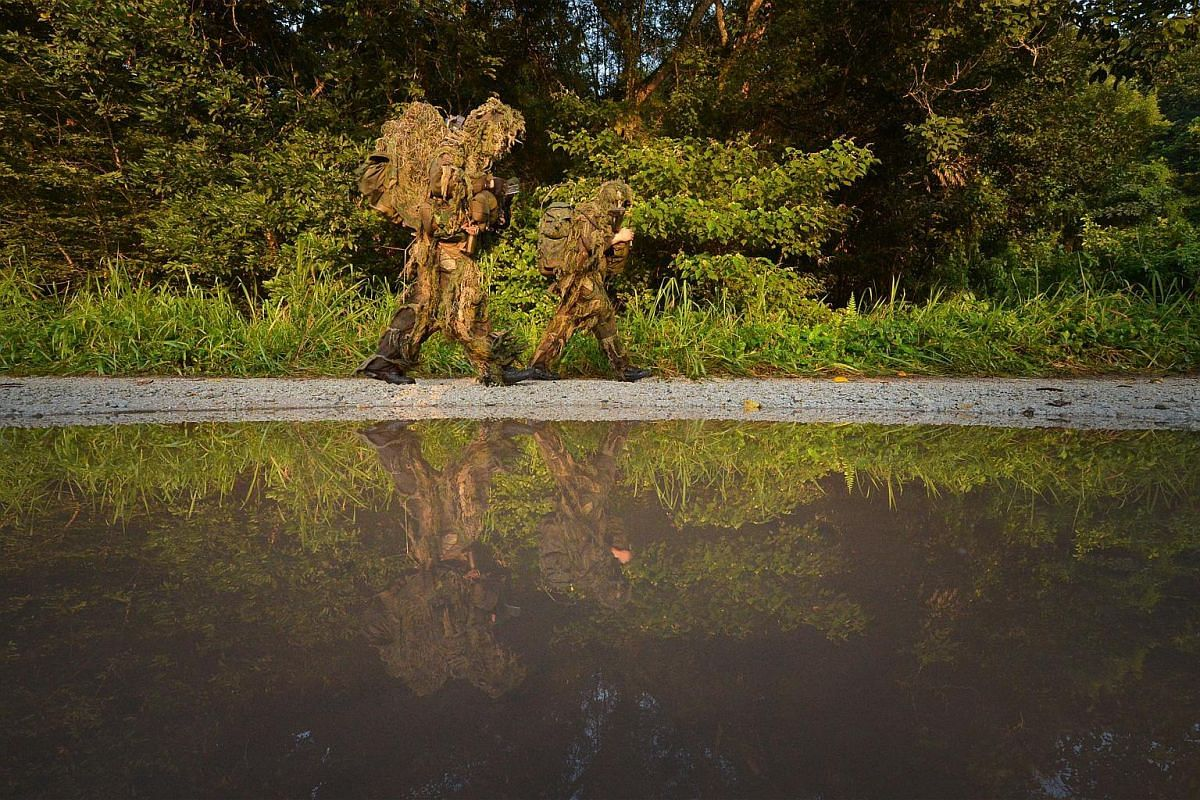 Clad in in their ghillie suits, a pair of snipers make their way along a gravel path to their training site in the early hours of the morning.