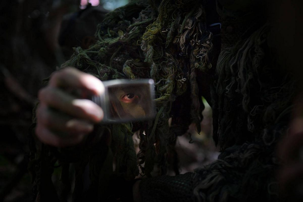 A sniper's eye is reflected on his mirror as he applies camouflage paint on the exposed parts of his body such as his face, neck, and hands to darken his features and blend into the background.