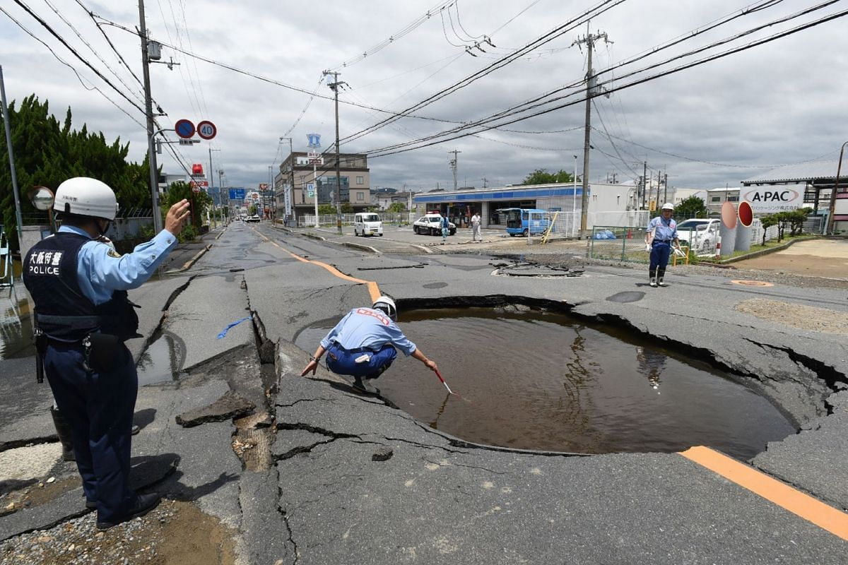 Police check a collapsed road following an earthquake in Takatsuki, north of Osaka prefecture on June 18, 2018. At least three people, including a child, were killed on June 18, after a strong quake rocked the second city of Osaka during the morning