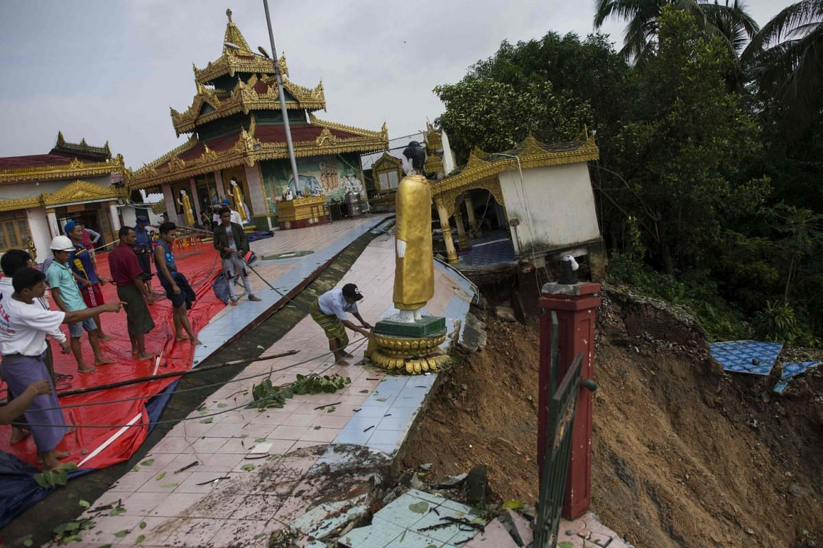Workers save a Buddha statue after a landslide damaged the hilltop Kyeik Than Lan pagoda in Mawlamyine capital of Mon state on June 18, 2018 following heavy rains. Flooding in southern Myanmar caused a landslide at the famed pagoda, submerged homes a