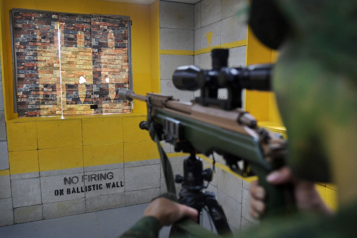 The final test of the Advanced Sniper Course is loophole firing, where trainees set up their hideout in a room and aim at a target through a gap in the ''wall'', which is simulated here by a plastic board. To pass the test, the sniper must successful