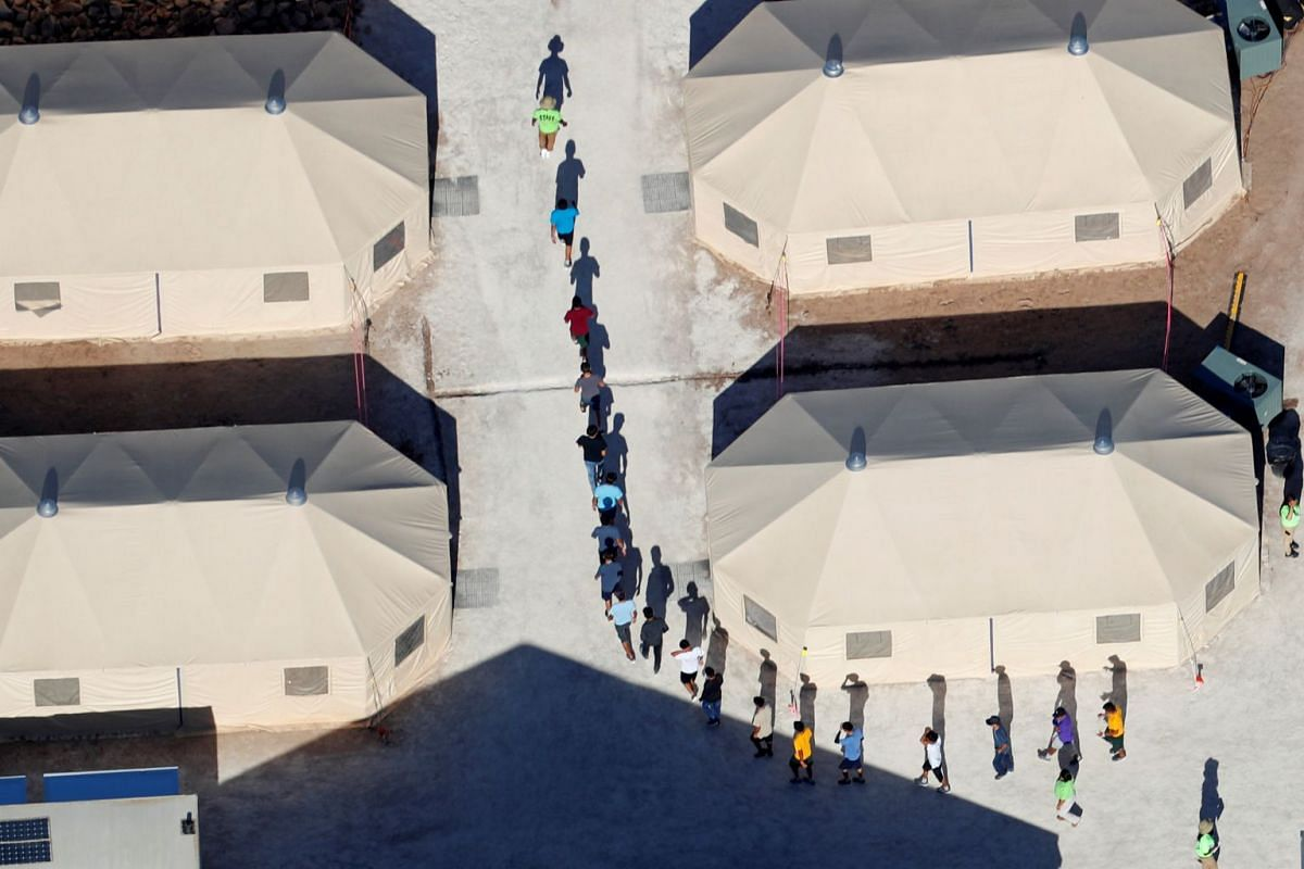 """Immigrant children, many of whom have been separated from their parents under a new """"zero tolerance"""" policy by the Trump administration, walk in single file between tents in their compound next to the Mexican border in Tornillo, Texas, U.S. June 18,"""