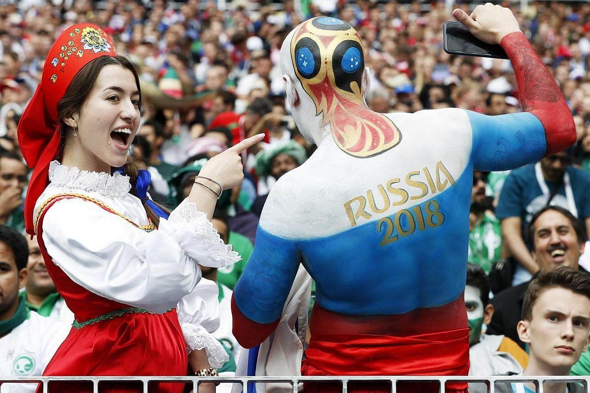 A Russian fan decked in a traditional outfit posing beside a man with the World Cup trophy painted at the back of his head before the match between Russia and Saudi Arabia in Moscow, on June 14, 2018.