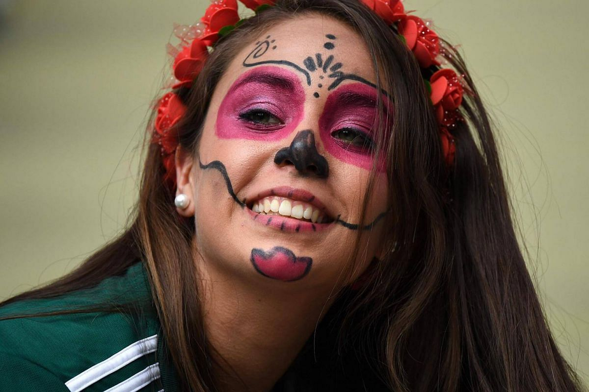 A Mexico fan with face paint smiling for the camera while waiting for the start of the Russia 2018 World Cup Group F football match between Germany and Mexico at the Luzhniki Stadium in Moscow, on June 17, 2018.