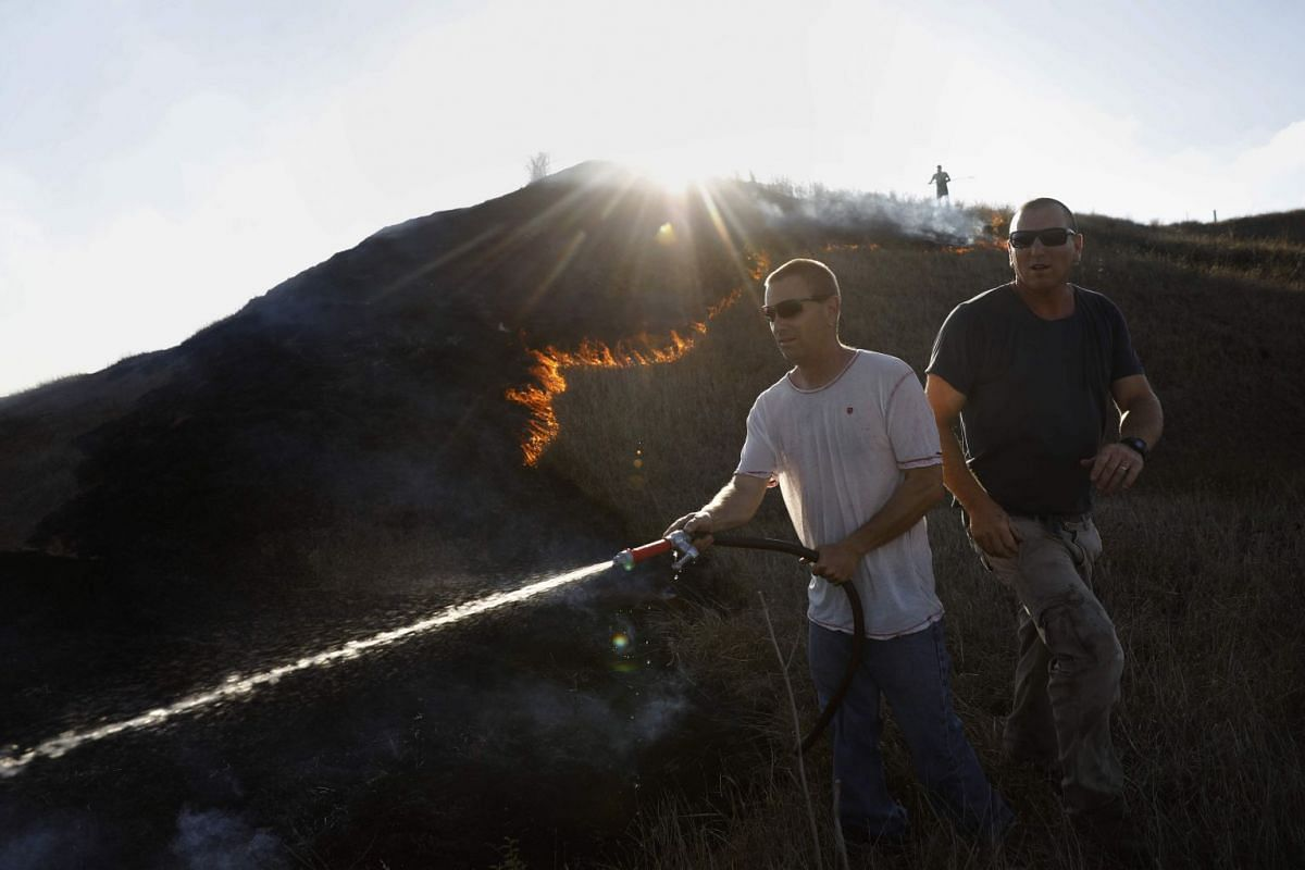 Israeli men extinguish a fire in a field next to Kibbutz Beeri reportedly caused by inflamable material attached to kites and flown across the border to Israel by activists in the Gaza strip on June 18, 2018. Kite-borne fire bombings have reportedly