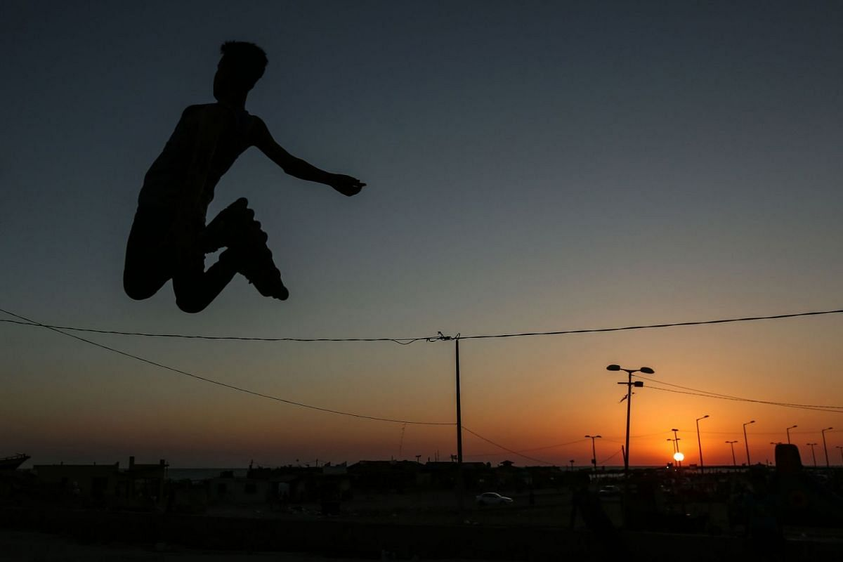 A Palestinian youth playing with rollerblades under the sunset at the sea port in Gaza City, on June 19, 2018. PHOTO: AFP