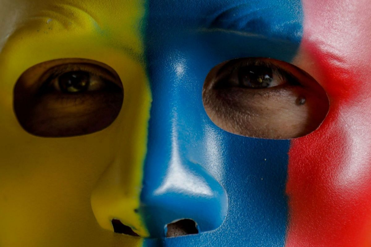 A Colombia supporter in Bogota's Corabastos Marketplace wearing a mask as he watches the FIFA World Cup Group H football match between Colombia and Japan, on June 19, 2018. PHOTO: AFP