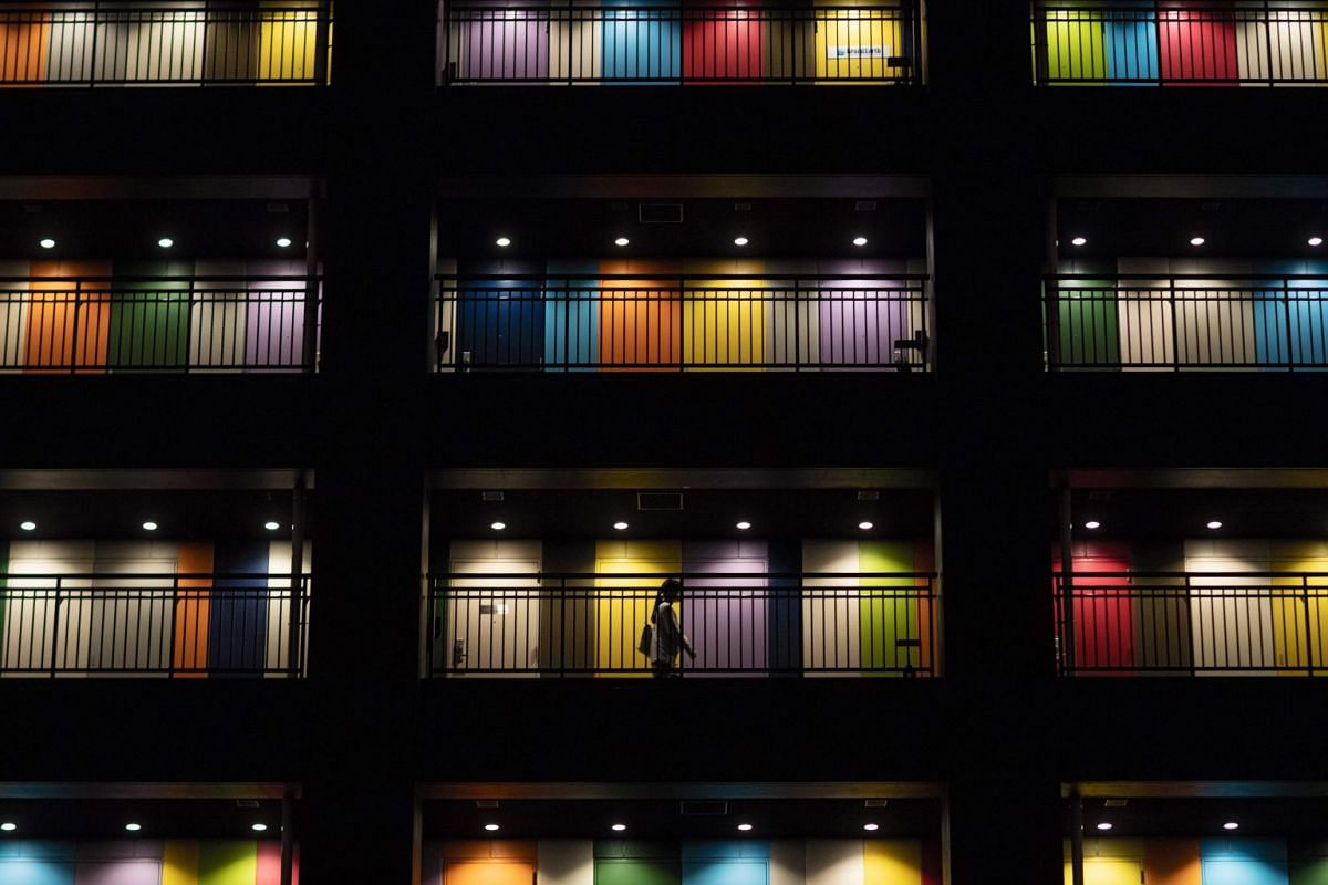 A woman walking along a passageway past apartments at a building in Tokyo, on June 19, 2018. PHOTO: AFP