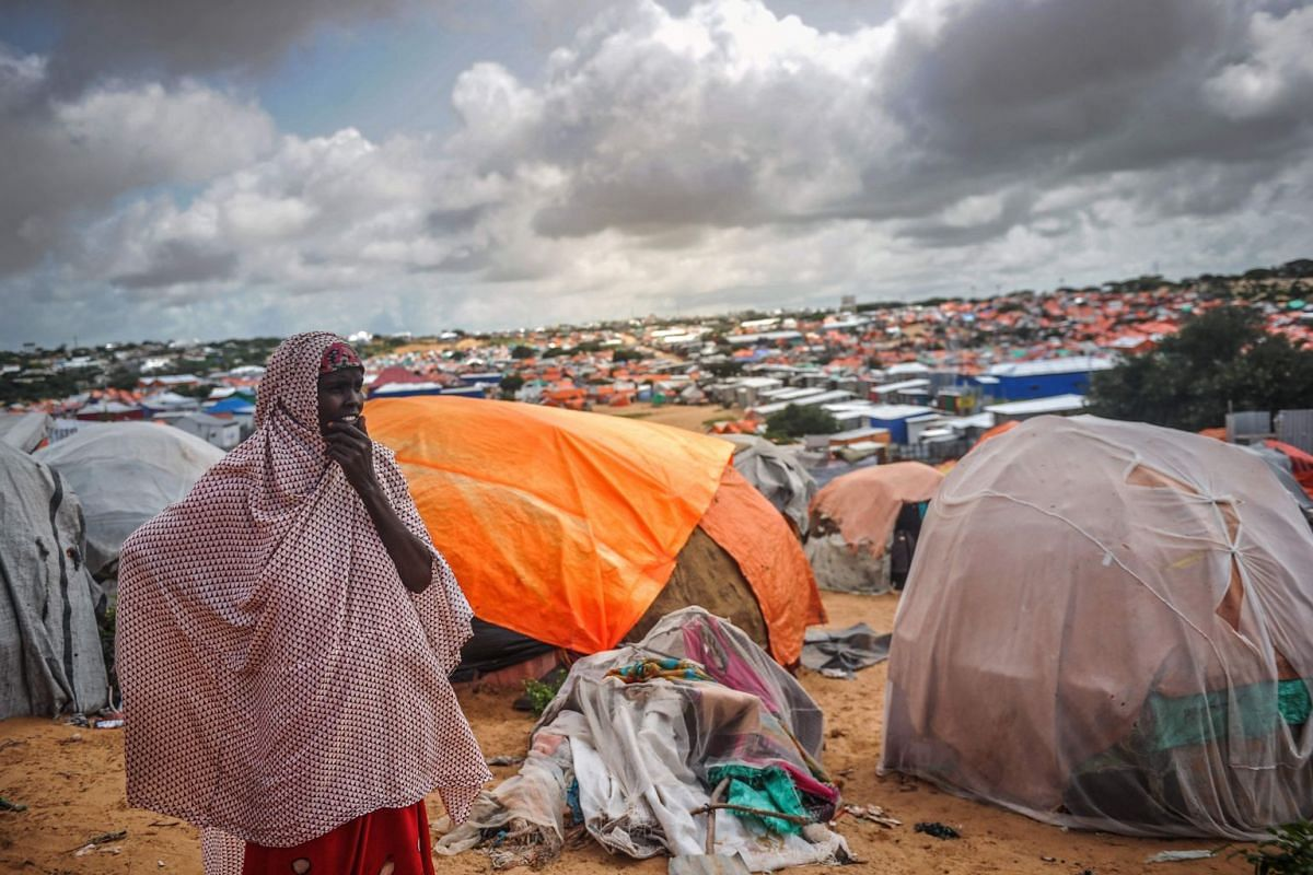 A Somali woman stands next to her makeshift tent at Tawakal IDP camp in Mogadishu, Somalia, on June 19, 2018. PHOTO: AFP