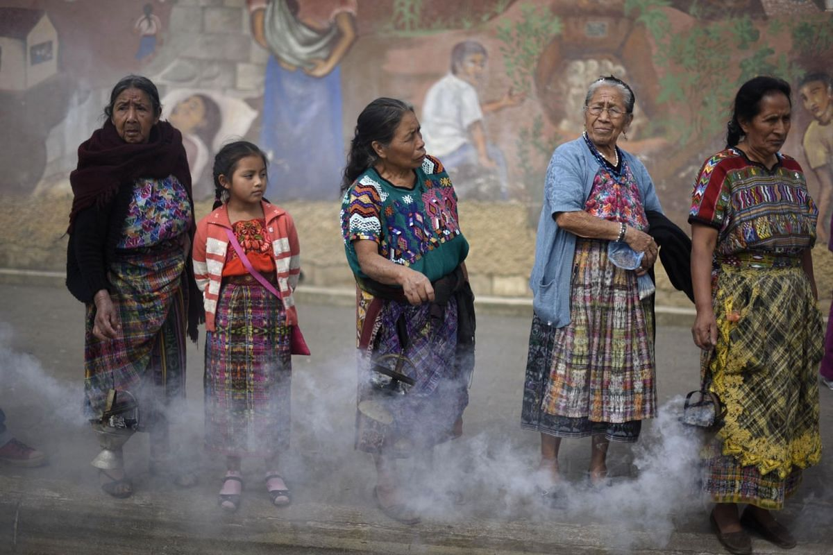 Indigenous women burn incense, as the truck transporting 172 urns containing the remains of victims of the Guatemalan armed conflict (1960-1996), arrives in San Juan Comalapa municipality, Chimaltenango department 35 km west of Guatemala City, where