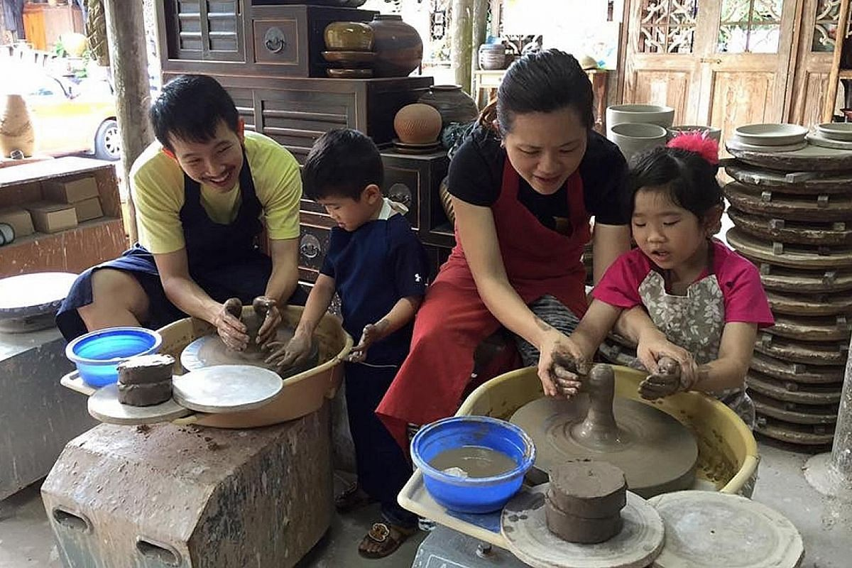 Mrs Raine Lee and her husband Max with their children - Alyssa, seven, and Titus, five - at a pottery-making workshop at Thow Kwang Pottery Jungle.