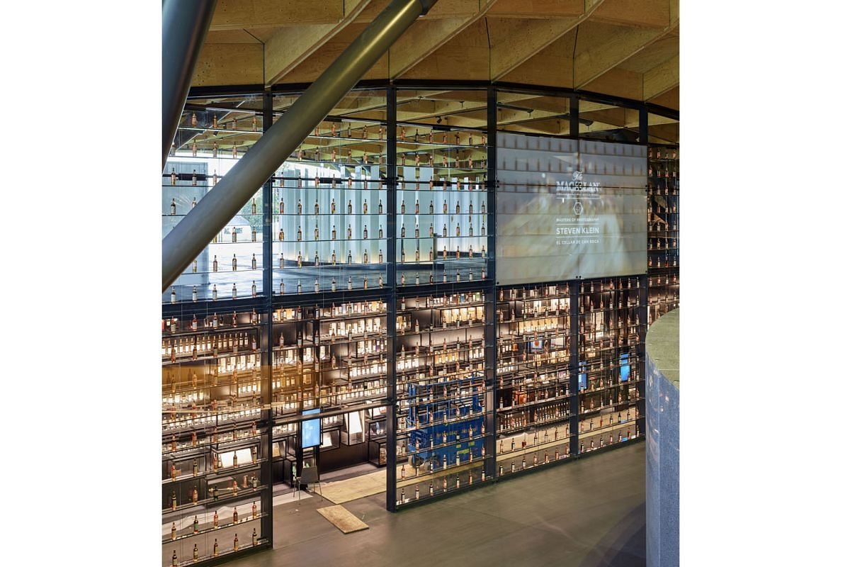 An 18m-tall glass wall at the entrance of the distillery contains 840 bottles from The Macallan's archives.