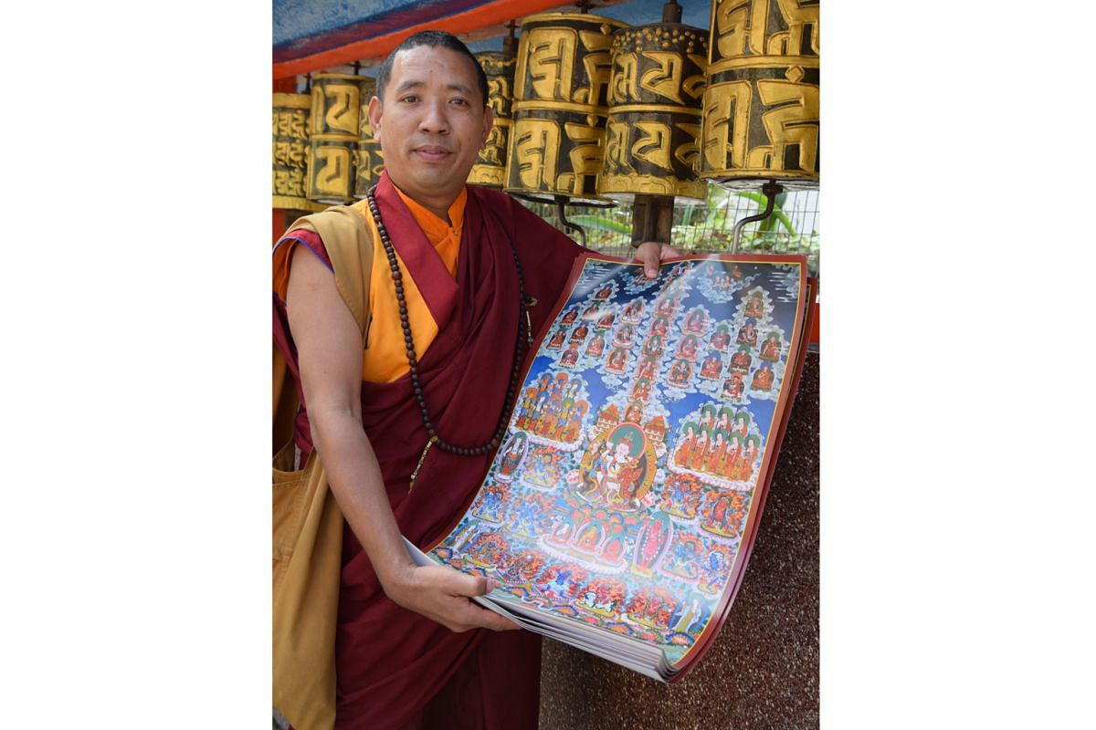 A lama (above) at a monastery unveiling a thangka, rolled out for display and worship on festive occasions.