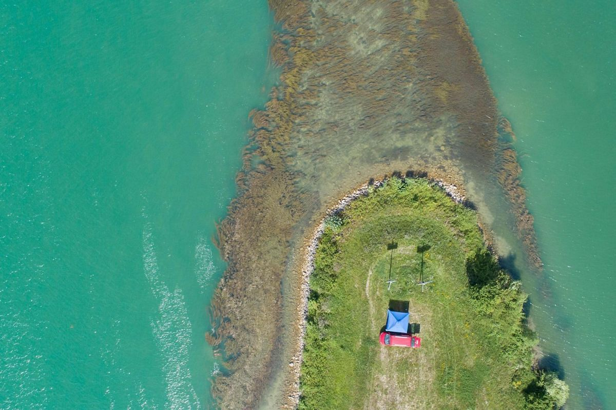 An aerial view showing a red van parked on a bank of the Rhin river in Wolfgantzen, eastern France, on June 24, 2018.