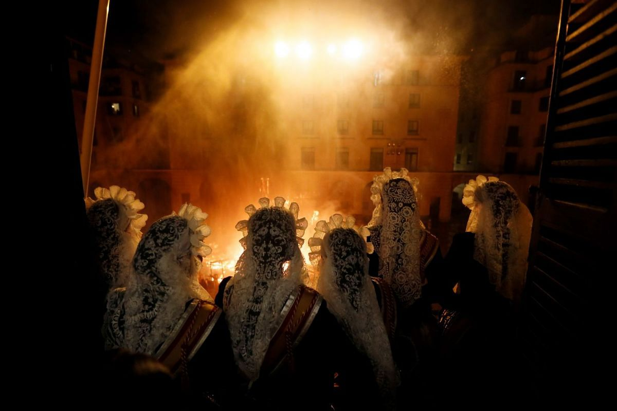 The Bella del Foc (Beauty of Fire) and her Ladies donning traditional costumes during the burning of official papier mache, cardboard and wooden sculpture from a balcony during the St. John Bonfires night, which is part of the St. John Festival in Al