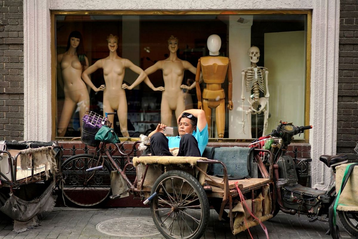 A man looking at his mobile phone on a tricycle outside a mannequin shop in Shanghai, China, on June 25, 2018.