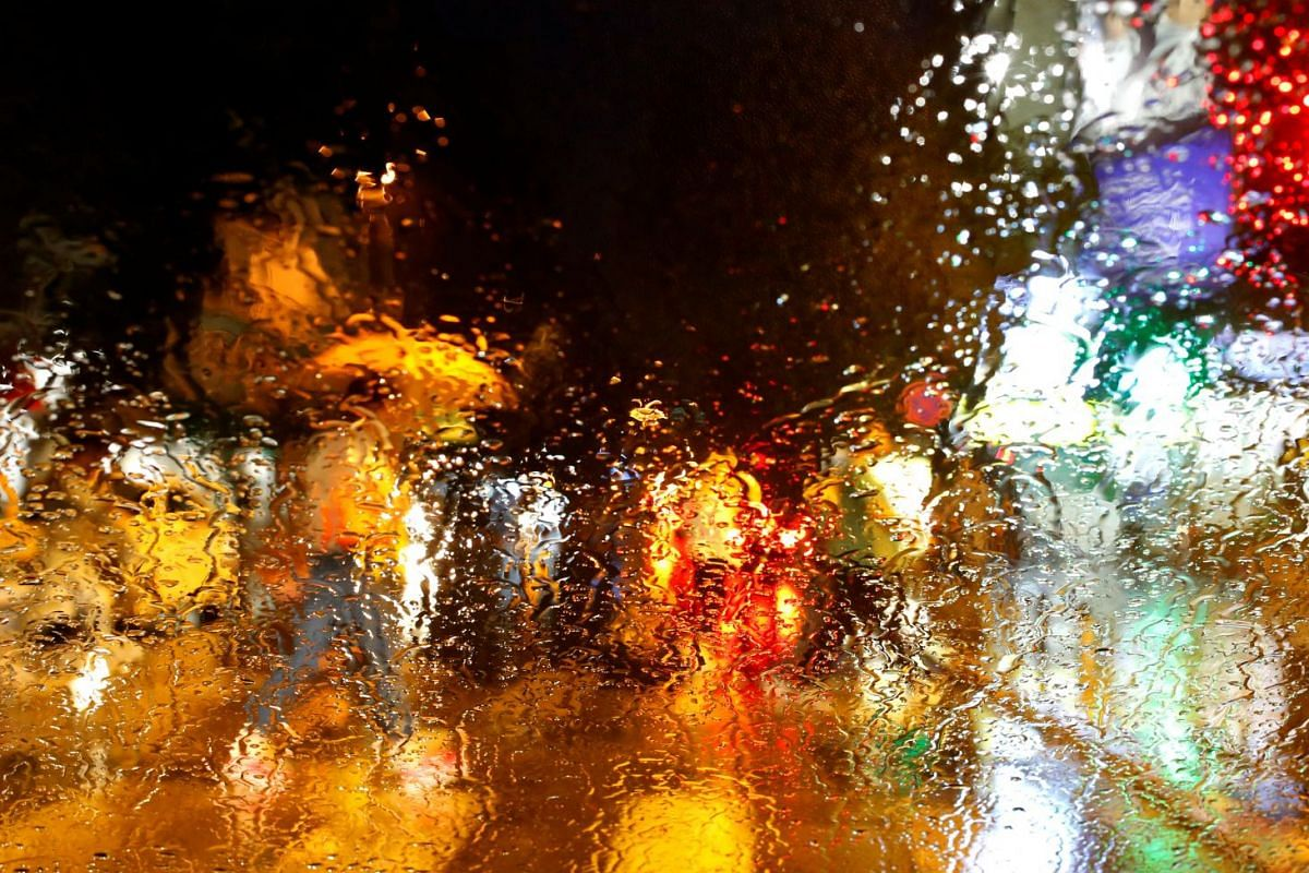 A man with an umbrella is seen through a car window covered with raindrops as he walks on the streets of Skopje, Macedonia, on June 25, 2018.