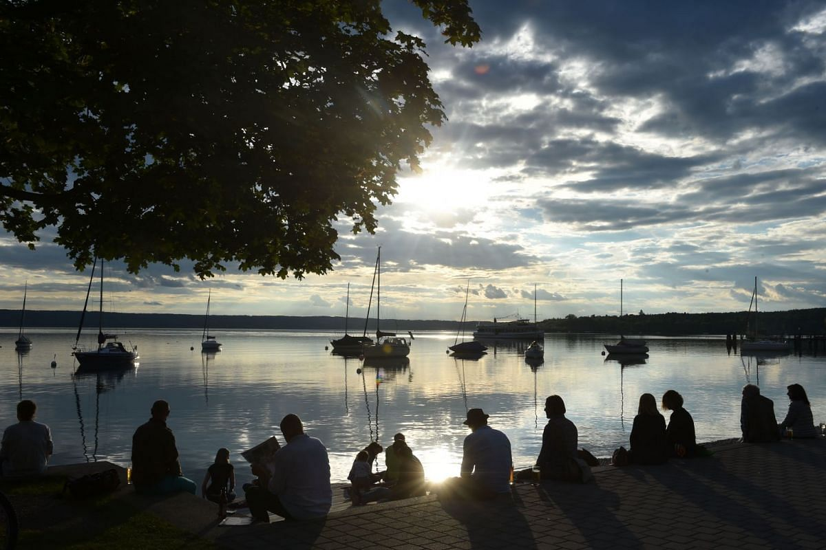 People enjoy the sunset near the Ammersee lake in the small Bavarian village of Herrsching, southern Germany where temperatures were reaching 22 deg C, on June 25, 2018.