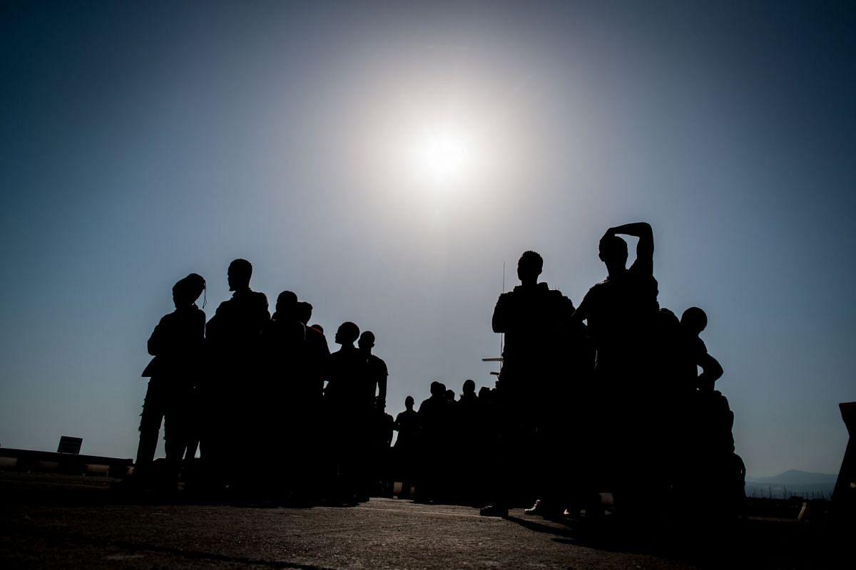 Migrants standing upon arrival at the port of Motril, southern Spain, after being intercepted aboard dinghies off the coast in the Mediterranean Sea, on June 26, 2018.